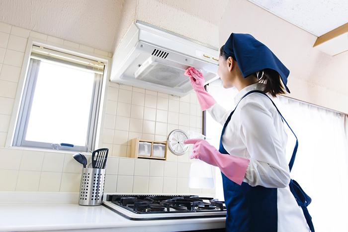 レンジフードを掃除する女性スタッフ