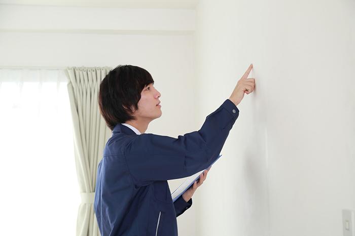 壁の汚れを点検する男性スタッフ